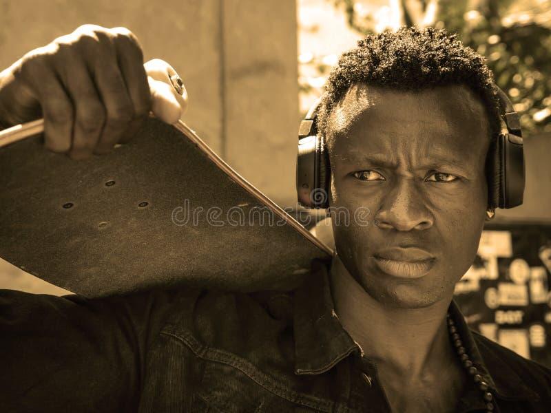 Homem americano novo isolado fresco do africano negro atrativo e seguro do moderno que anda na placa do patim da terra arrendada  fotografia de stock royalty free