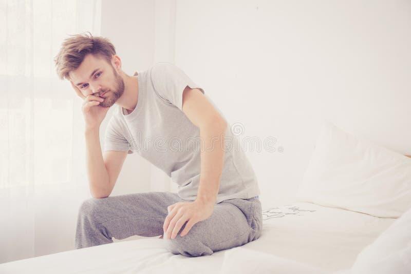 Homem americano que boceja O homem que senta uma cama é sério e problema fotografia de stock royalty free