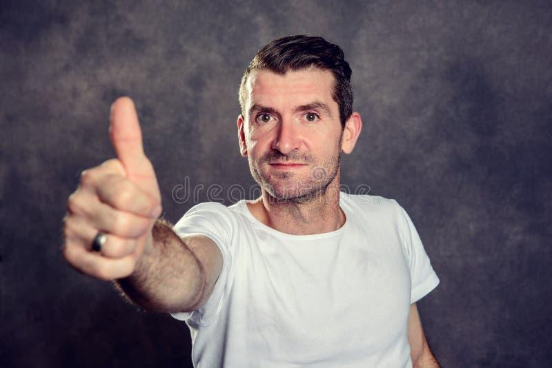 Homem amig?vel com polegar acima na frente do fundo cinzento imagens de stock royalty free