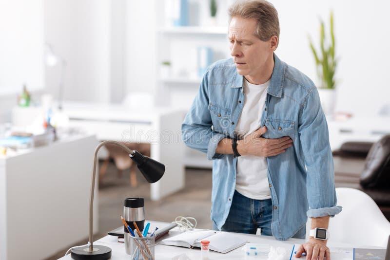 Homem ansioso que tem o cardíaco de ataque fotos de stock