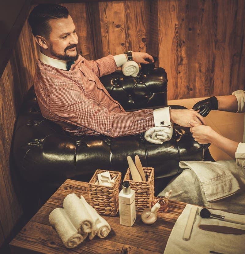 Homem antiquado seguro que faz o tratamento de mãos masculino em uma barbearia fotografia de stock