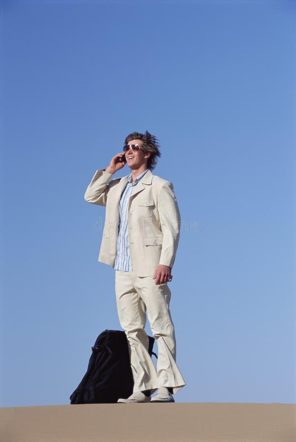 Homem ao ar livre com mala de viagem usando o telemóvel imagens de stock