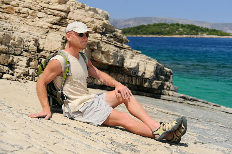 Homem ao ar livre que descansa na rocha após a caminhada fotos de stock royalty free