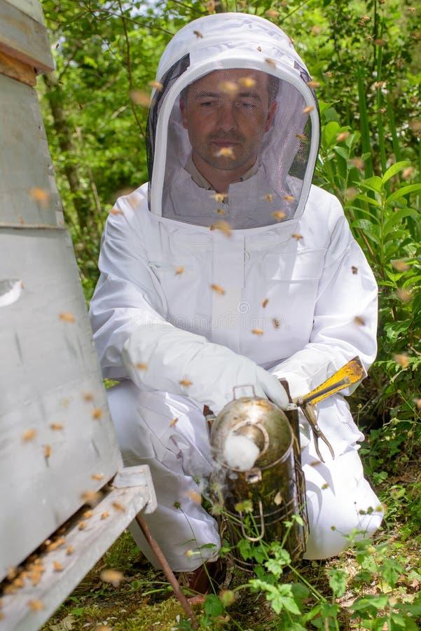 Homem ao lado da colmeia da abelha fotografia de stock