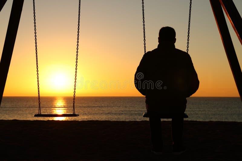 Homem apenas que olha o por do sol na praia fotografia de stock