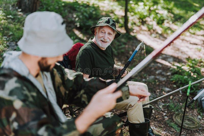 Homem aposentado alegre que aprecia a pesca com seu filho imagem de stock