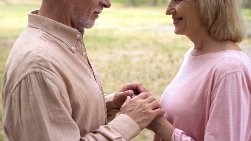Homem aposentado considerável que cobre as mãos fêmeas, data romântica no parque, ternura fotografia de stock royalty free