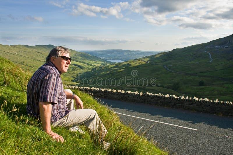 Homem aposentado que descansa perto da estrada imagens de stock