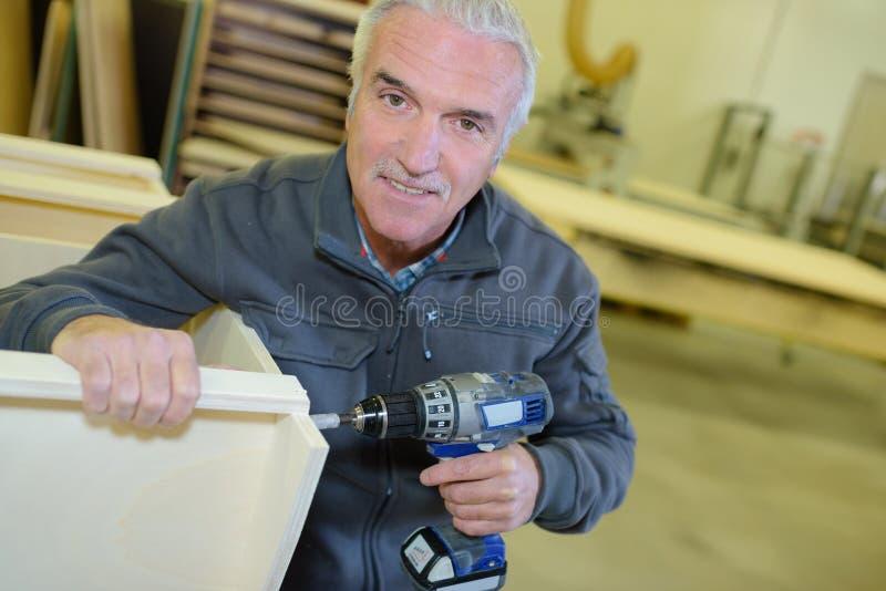 Homem aposentado retrato que trabalha na oficina imagem de stock