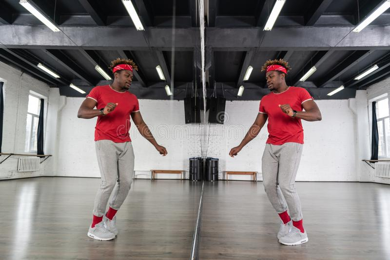 Homem apto ativo na dança desportivo do equipamento na frente do espelho fotos de stock royalty free