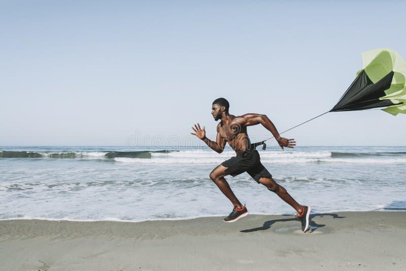 Homem apto com um paraquedas running na praia imagem de stock royalty free