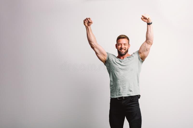 Homem apto considerável que aumenta seus braços no gesto de vencimento imagem de stock