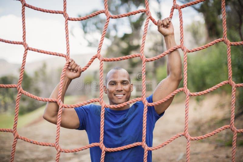Homem apto de sorriso que escala uma rede durante o curso de obstáculo imagens de stock royalty free