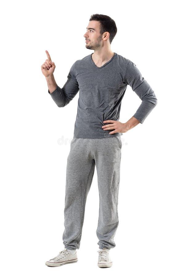 Homem apto do esporte em calças de suor e na camisa cinzenta que aponta o dedo que olha acima o copyspace imagens de stock royalty free