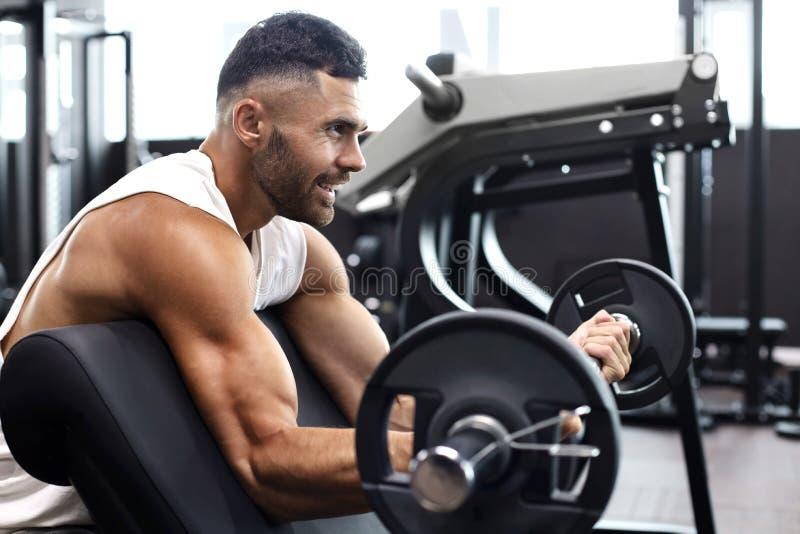 Homem apto e muscular que levanta o peso pesado do barbell usando o banco no gym imagem de stock royalty free