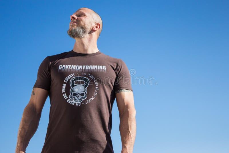 Homem apto na camisa de Brown Kettlebell imagens de stock royalty free