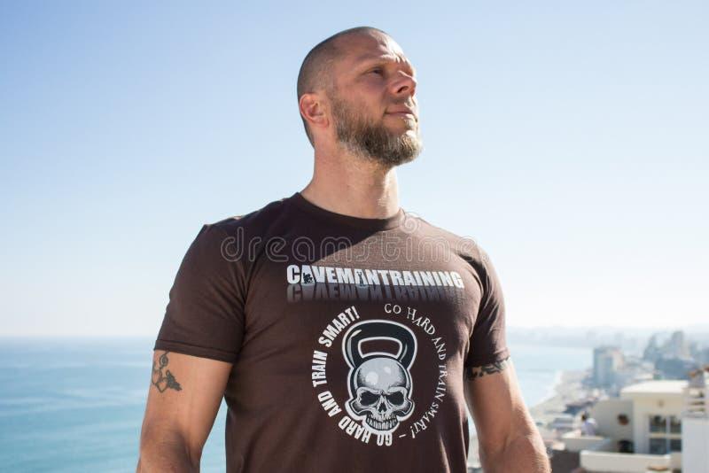 Homem apto na camisa de Brown Kettlebell foto de stock royalty free