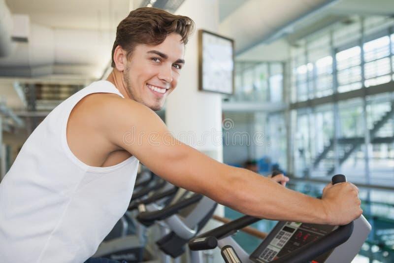 Homem apto que dá certo na bicicleta de exercício imagem de stock royalty free