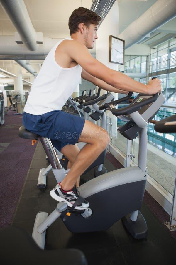 Homem apto que dá certo na bicicleta de exercício fotos de stock