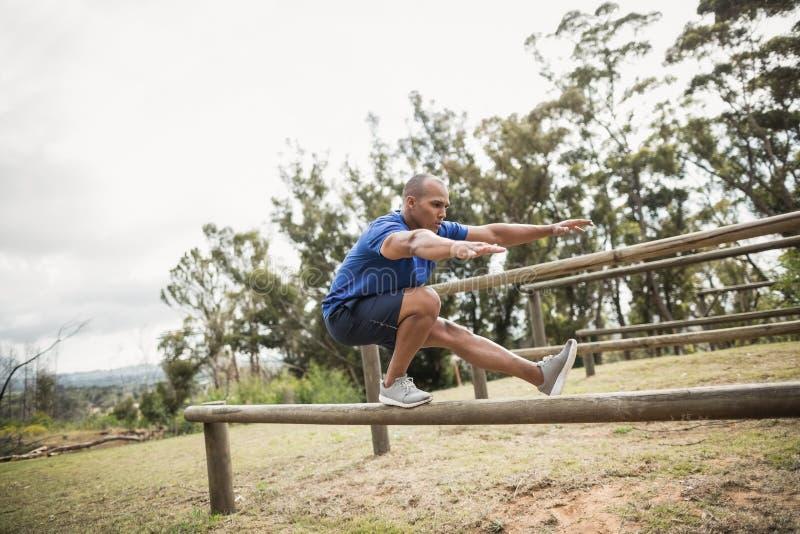 Homem apto que equilibra em obstáculos durante o treinamento do curso de obstáculo fotografia de stock royalty free