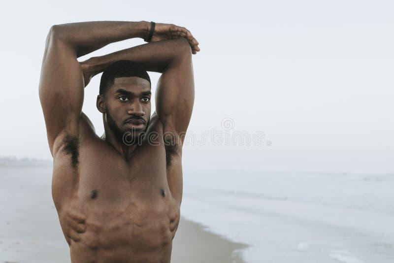 Homem apto que estica na praia imagens de stock royalty free