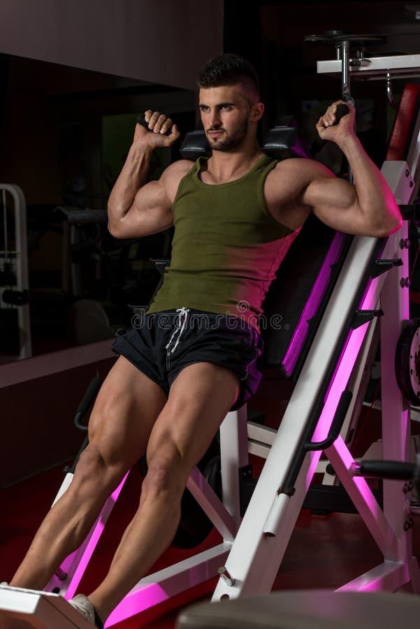 Homem apto que usa a máquina da imprensa do pé em um health club imagem de stock