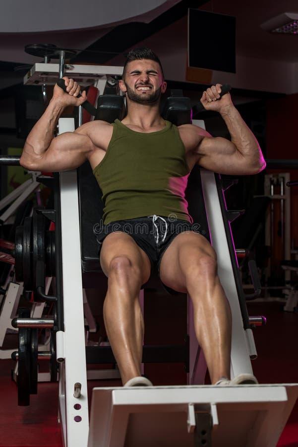 Homem apto que usa a máquina da imprensa do pé em um health club imagem de stock royalty free