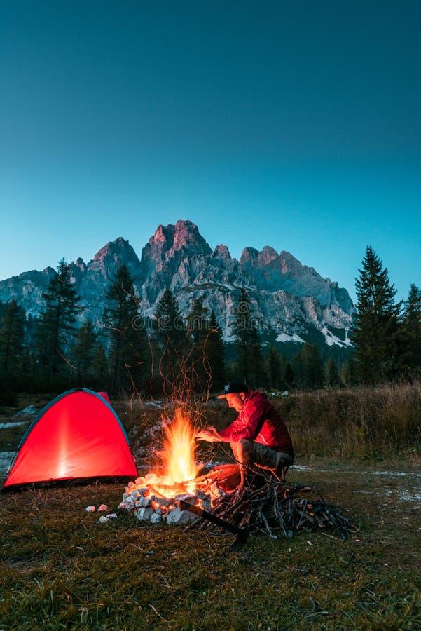 Homem Aquecendo Mãos por Campfire em Montanhas Tonelada iluminada vermelha no acampamento imagens de stock