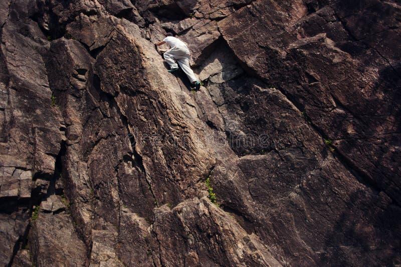 Homem arriscado que escala sobre a montanha do perigo sem chicote de fios e corda de segurança foto de stock