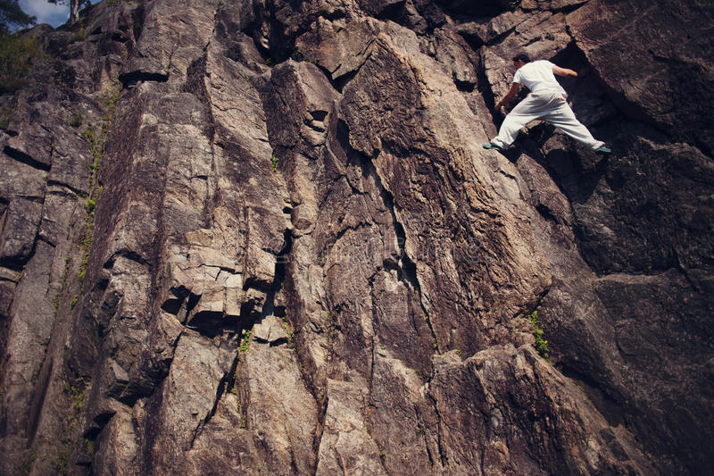 Homem arriscado que escala sobre a montanha do perigo sem corda imagem de stock