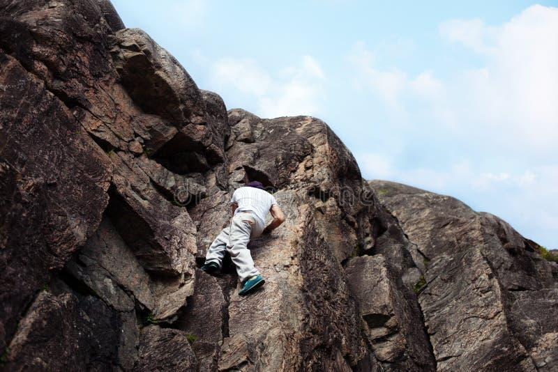 Homem arriscado que passa sobre a montanha do perigo sem corda da segurança fotografia de stock