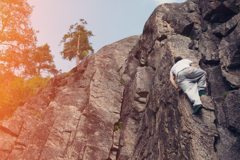 Homem arriscado que passa sobre a montanha do perigo sem corda e chicote de fios da segurança imagem de stock