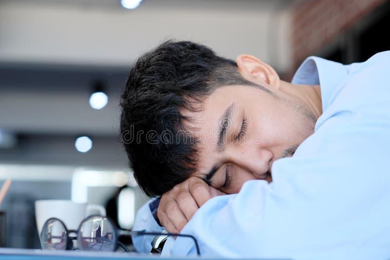 Homem asiático cansado que dorme na mesa de escritório O homem de negócios novo com monóculos sobrecarregou e caiu homem ocasiona imagens de stock