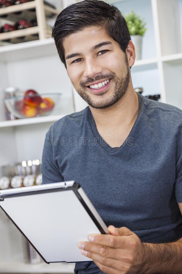 Homem asiático com barba usando o tablet pc na cozinha foto de stock royalty free