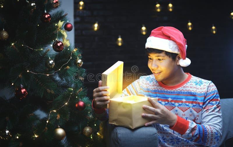 Homem asiático com o presente de brilho de abertura do traje do Natal, sentando-se ao lado da árvore de Natal foto de stock