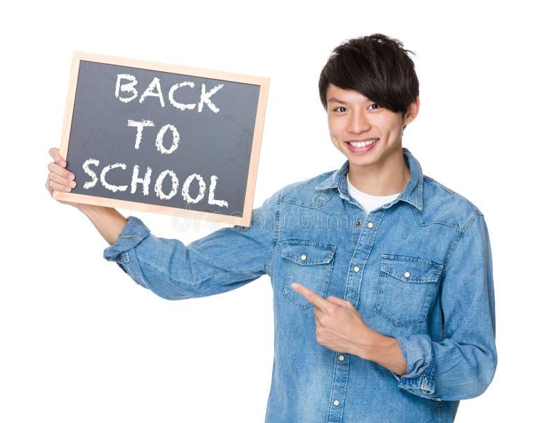 Homem asiático com o quadro-negro que mostra frases de volta à escola fotografia de stock