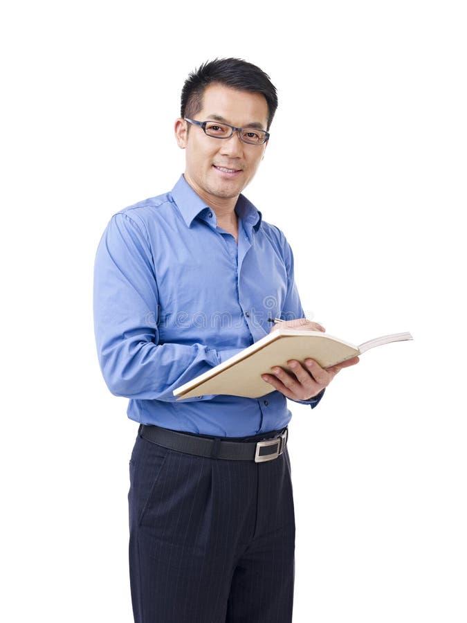 Homem asiático com pena e caderno fotografia de stock royalty free