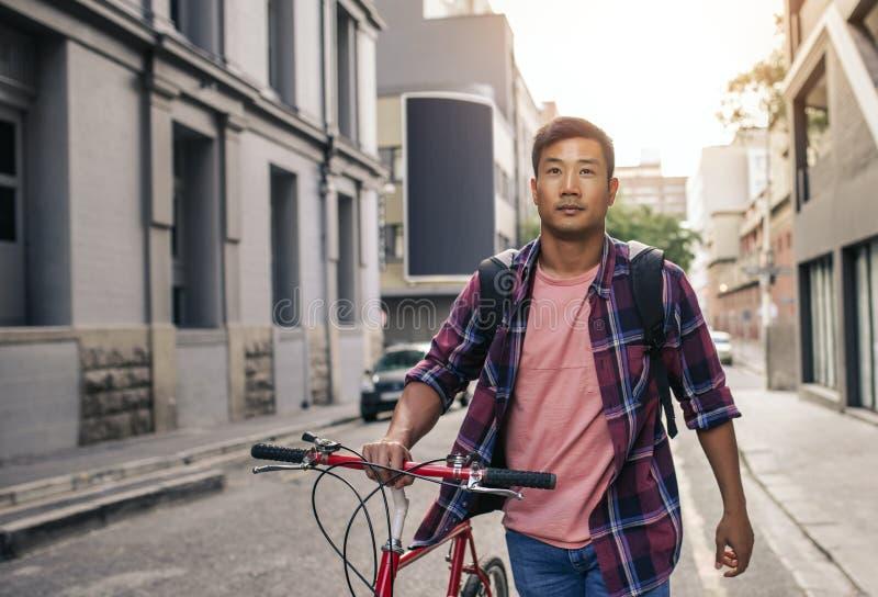 Homem asiático considerável que anda com sua bicicleta através das ruas da cidade foto de stock