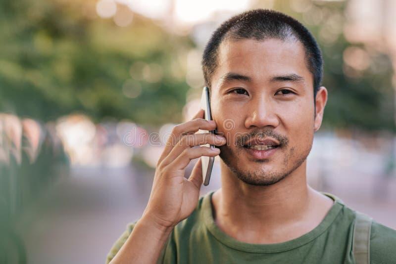 Homem asiático considerável que fala em seu telefone celular fora imagens de stock royalty free