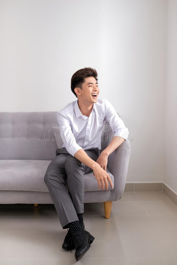 Homem asiático considerável que senta-se em casa no sofá, sorriso feliz fotografia de stock royalty free