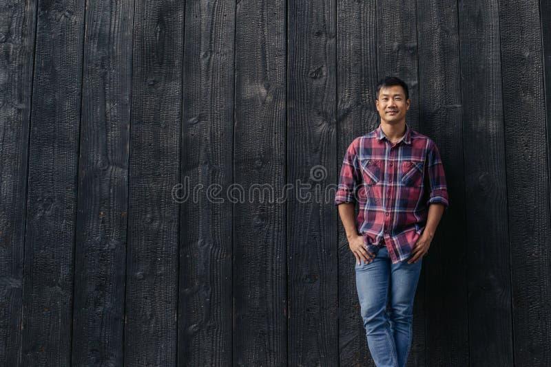 Homem asiático considerável que sorri ao inclinar-se contra uma parede fora fotografia de stock