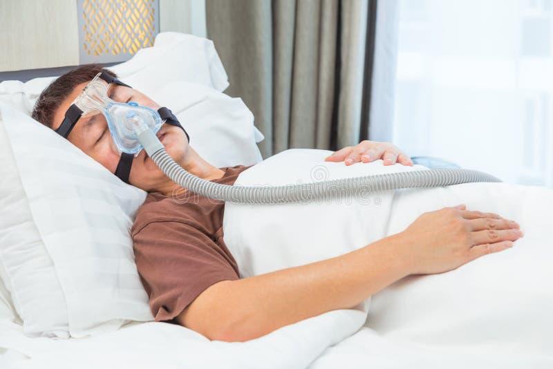 Homem asiático da Idade Média que dorme em sua cama que veste o conne da máscara de CPAP foto de stock royalty free