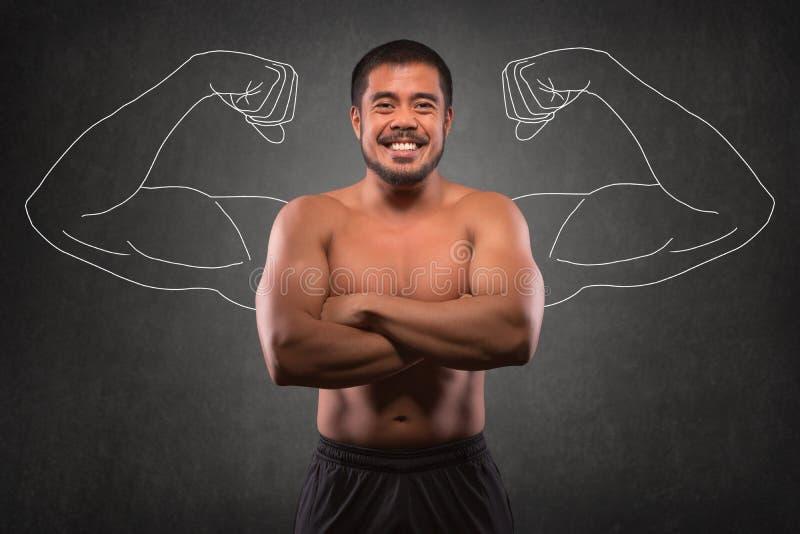 Homem asiático de sorriso com parte superior do corpo muscular na frente do fundo dos braços do músculo Aptidão, exercício e conc fotos de stock royalty free