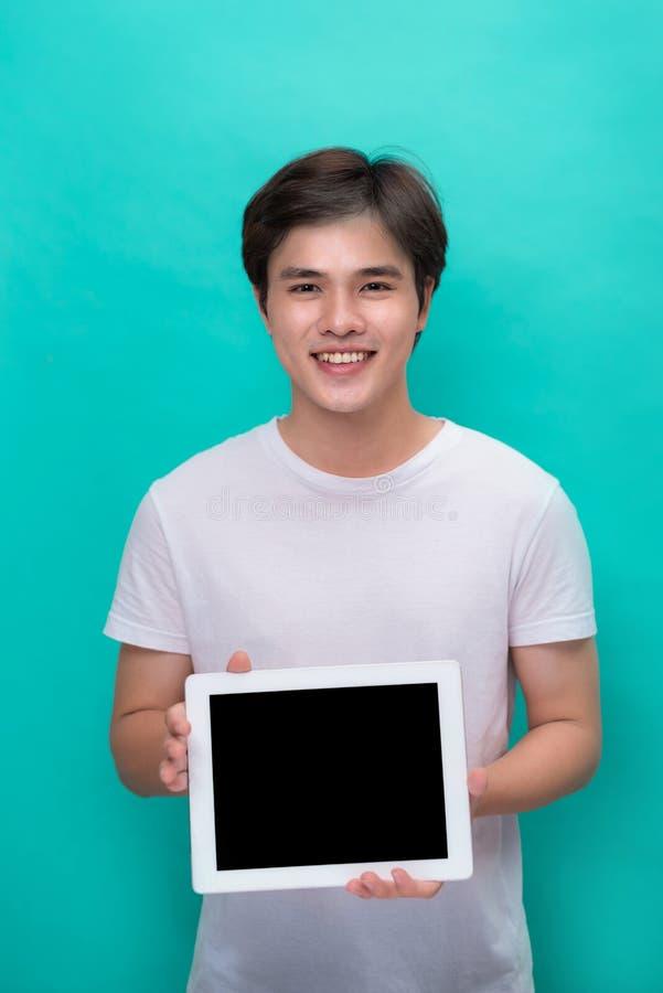 Homem asiático de sorriso que mostra a tela de tablet pc vazia sobre o azul imagem de stock royalty free