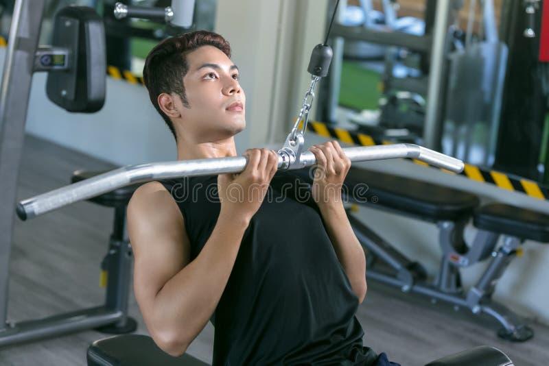 Homem asiático do esporte que faz elevações Treinamento do Bodybuilder na ginástica foto de stock royalty free