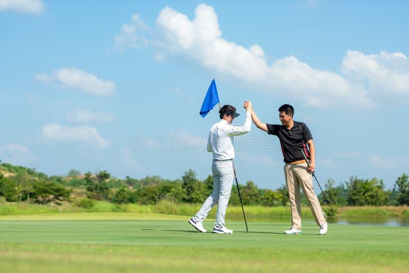 Homem asiático do Grupo Professional Golfer aperta a mão pela amizade depois de terminar coloca bola em verde Relaxe do hobby nas imagens de stock royalty free
