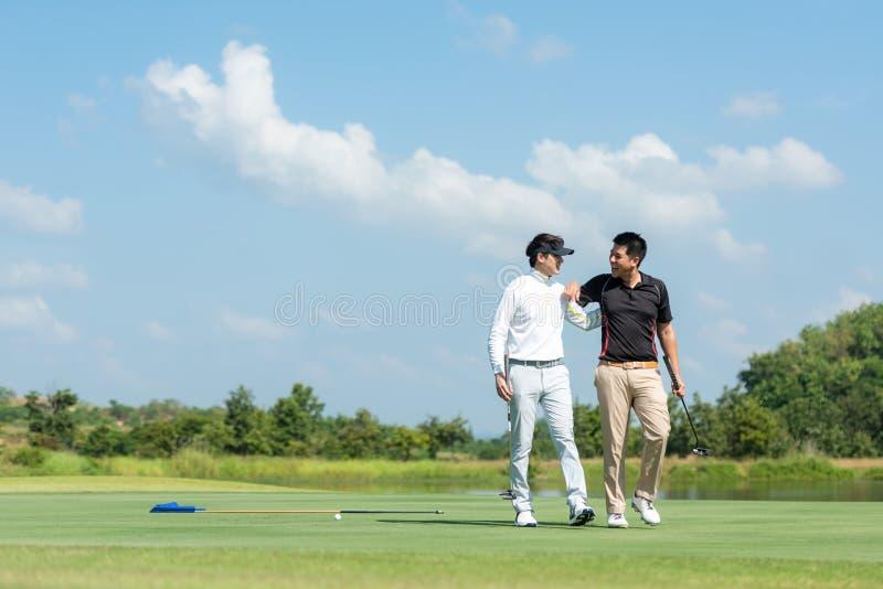 Homem asiático do Grupo Professional Golfer caminhando e abraçando por amizade depois de terminar, coloque bola em verde Hobby em fotografia de stock royalty free