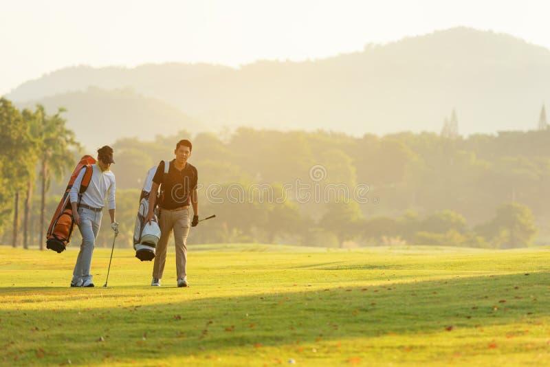 Homem asiático do Grupo Professional Golfer caminhando na via navegável com golfe de saco com clube multiétnico Hobby em férias e imagens de stock royalty free