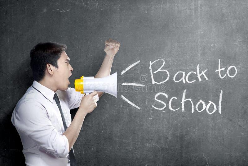 Homem asiático do professor que usa o megafone para notificar para para ir para trás à escola com fundo do quadro-negro fotos de stock royalty free