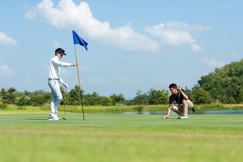 Homem asiático e amigo do Grupo Professional Golfer jogando tiro no alvo para colocar bola no buraco com clube no campo verde Hob fotografia de stock